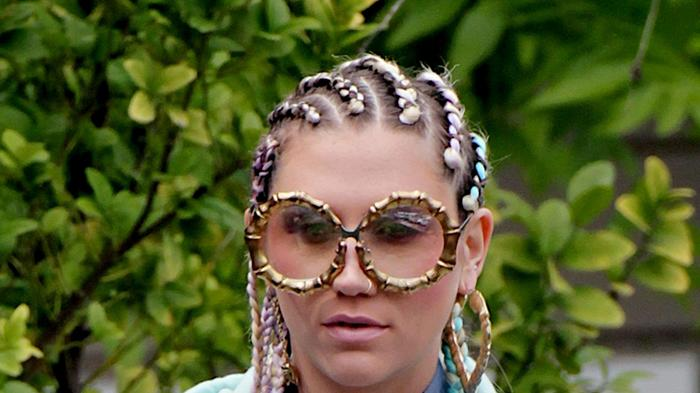 Ke$ha goes gangster nerd as she rocks gold chain glasses that appear to connect to a corn row hairpiece in Los Angeles