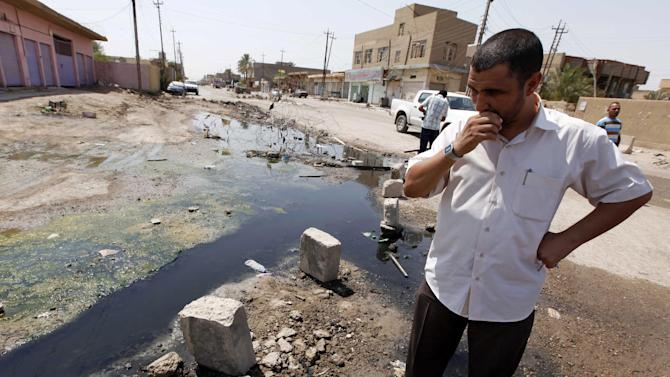 FILE - In this Sunday, Aug. 15, 2010 file photo, a man stands in a sewage-filled street in Fallujah, Iraq, 40 miles (65 kilometers) west of Baghdad. Ten years and $60 billion in taxpayer funds later, Iraq is still so unstable and broken that even its leaders question whether U.S. efforts to rebuild it were worth the cost. A $108 million waste water treatment center in the city of Fallujah, a former al-Qaida stronghold in western Iraq, will have taken eight years longer to build than planned when it is completed in 2014 and will only service 9,000 homes. Iraqi officials must provide an additional $87 million to hook up most of the rest of the city, or 25,000 additional homes. (AP Photo/Hadi Mizban, File)