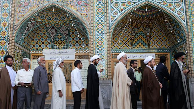 Men wait in line at a polling station to vote during presidential elections in Qom, 125 kilometers (78 miles) south of the capital Tehran, Iran, Friday, June 14, 2013. (AP Photo/Ebrahim Noroozi)