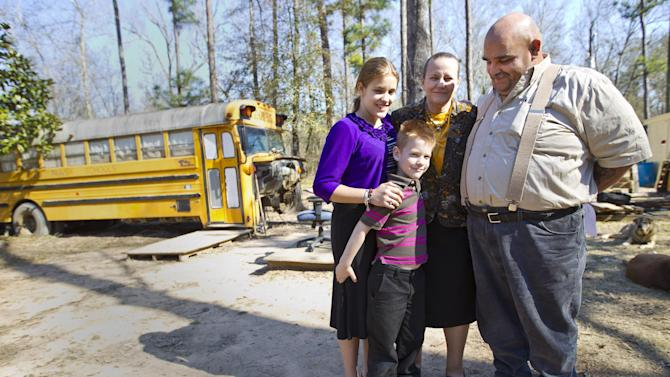 Sherrie, second right, and Mark Shorten, right, pose for photos with their children, 12, left, and Chance, 6, in front of their home, a converted school bus, in Splendora, Texas on Tuesday, Jan. 22, 2013. Nearly a year after their two children were found living virtually unsupervised in the old school bus, the Shortens regained full custody of their kids Tuesday when a judge dismissed a child welfare case against them. (AP Photo/Houston Chronicle, Karen Warren) MANDATORY CREDIT