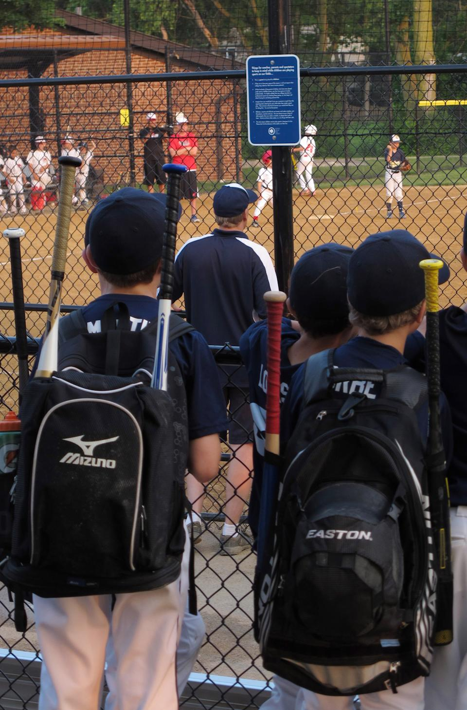 Young players wait for a game near a sign on a fence about parent behavior in Buffalo Grove, Ill. on Monday, June 10, 2013. Earlier in the month, park district officials in the Chicago suburb posted the signs asking parents to behave and keep the games in perspective. (AP Photo/Martha Irvine)