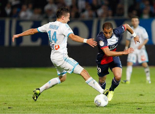 Paris Saint Germain's Brazilian midfielder Lucas, right, challenges for the ball with Marseille's French midfielder Florian Thauvin, during their League One soccer match, at the Velodrome Stadium, in
