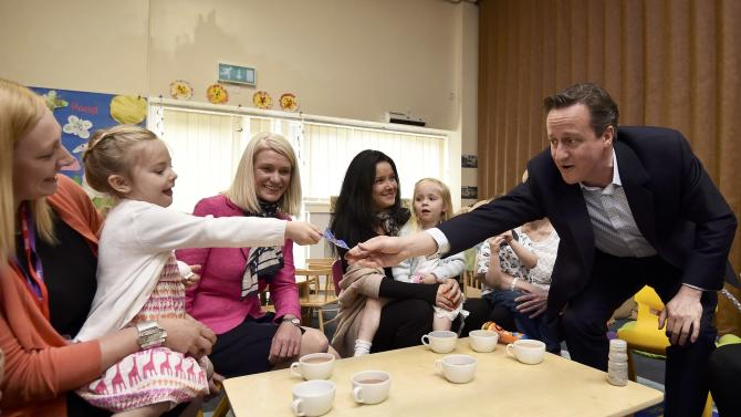 Britain's Prime Minister David Cameron receives a gift froma child at a nursery during a campaign visit to Cannock, central England
