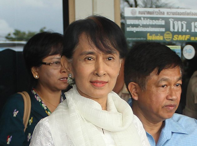 Myanmar's opposition leader Aung San Suu Kyi is escorted to a waiting car upon her arrival at Mae Sot airport near the Thai-Myanmar border Saturday, June 2, 2012. Suu Kyi turned her attention to Myanmar's long-standing refugee crisis Saturday with a visit to a sprawling camp on Thailand's border to get her first glimpse of the hardships faced by hundreds of thousands who have fled war in her homeland. (AP Photo/Apichrt Weerawong)