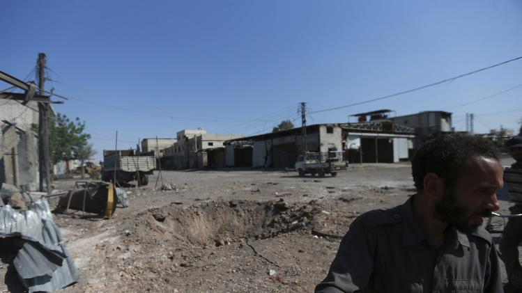 A man inspects a site hit by what activists said was an airstrike by forces loyal to Syria's President Bashar al-Assad on the outskirts of the Duma neighbourhood of Damascus