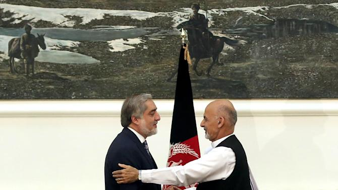 Afghanistan's presidential election candidates Abdullah Abdullah, left, and Ashraf Ghani Ahmadzai, right, shake hands after signing a power-sharing deal at the presidential palace in Kabul, Afghanistan, Sunday, Sept. 21, 2014. Afghanistan's two presidential candidates signed a power-sharing deal Sunday, capped with a hug and a handshake, three months after a disputed runoff that threatened to plunge the country into turmoil and complicate the withdrawal of U.S. and foreign troops. (AP Photo/Massoud Hossaini)