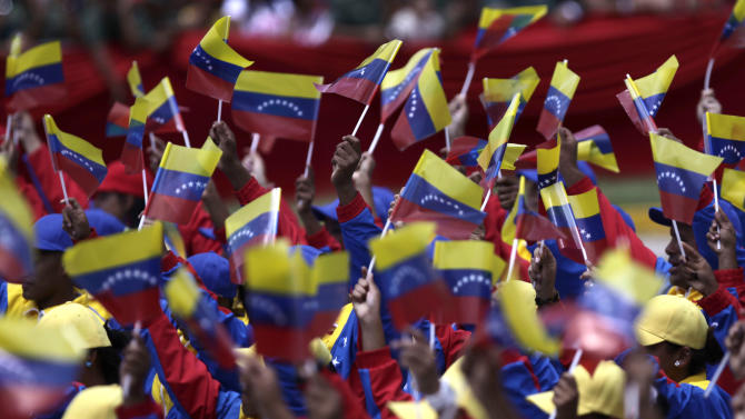 People wave Venezuelan flags during a parade marking 200 years of Venezuela's independence in Caracas, Venezuela, Tuesday July 5, 2011.  Ailing Venezuelan President Hugo Chavez stayed home in his presidential palace Tuesday while thousands of troops across town marched to mark the country's bicentennial. Venezuela declared its independence from Spain in 1811. (AP Photo/Ariana Cubillos)