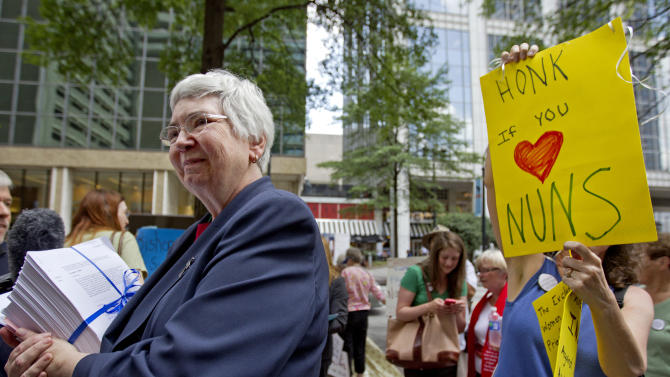 """Sister Mary Ann Walsh, left, director of media relations for the U.S. Conference of Catholic Bishops, accepts a petition from supporters of U.S Catholic nuns as a demonstrator stands at right, at the U.S. Bishops' biannual meeting Wednesday, June 13, 2012, in Atlanta. Supporters of U.S. Catholic nuns hand delivered the petition in response to a recent Vatican finding, which accused them of promoting """"certain radical feminist themes incompatible with the Catholic faith,"""" while failing to emphasize core teaching on abortion. The Vatican ordered a full-scale overhaul of the organization overseen by three American bishops, a decision that has led to an outpouring of support for the nuns nationwide. (AP Photo/David Goldman)"""