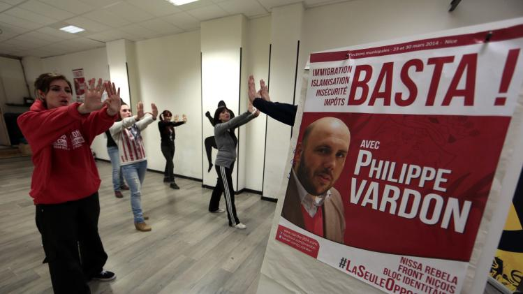 Women practice a self defence course next to a campaign poster of Philippe Vardon, president of the French far-right group Nissa Rebela, in Nice