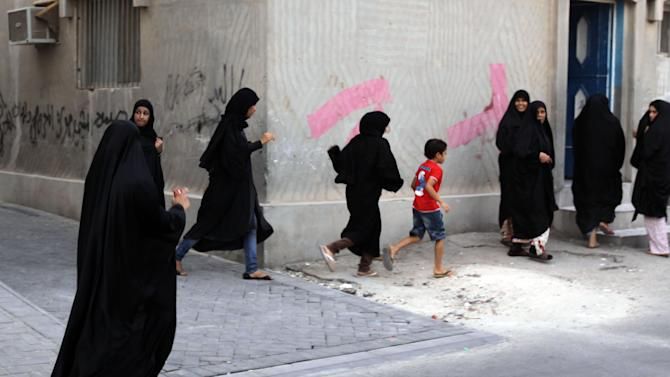 Women and children run as riot police, unseen, chase Bahraini anti-government protesters Wednesday, June 20, 2012, in Malkiya village, Bahrain. Clashes erupted after riot police fired tear gas to disperse people gathering for a march in support of political prisoners. (AP Photo/Hasan Jamali)