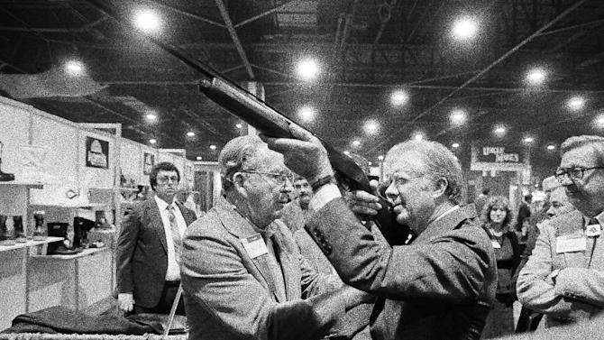 FILE - In this Nov. 14, 1984 file photo, former President Jimmy Carter sights down the barrel of a shotgun as Reinhart Fajen, a gunstock manufacturer checks the fit, in Atlanta as Carter stopped during a visit to the national shooting sports foundation shot show at the World Congress center. (AP Photo/Ric Feld)