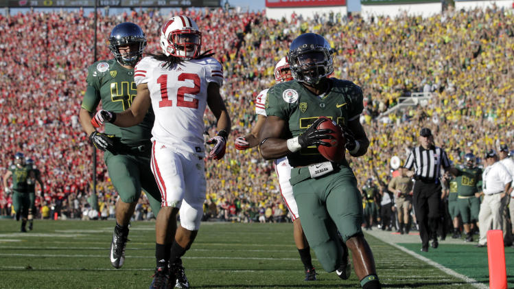 Oregon's Kenjon Barner scores a touchdown during the first half of the Rose Bowl NCAA college football game against Wisconsin on Monday, Jan. 2, 2012, in Pasadena, Calif. Wisconsin defensive back Dezmen Southward (12) trails on the play. (AP Photo/Jae C. Hong)