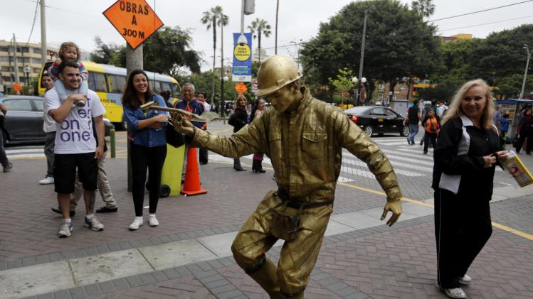 A street artist acts as a statue of a construction worker along a street in Lima's Miraflores district