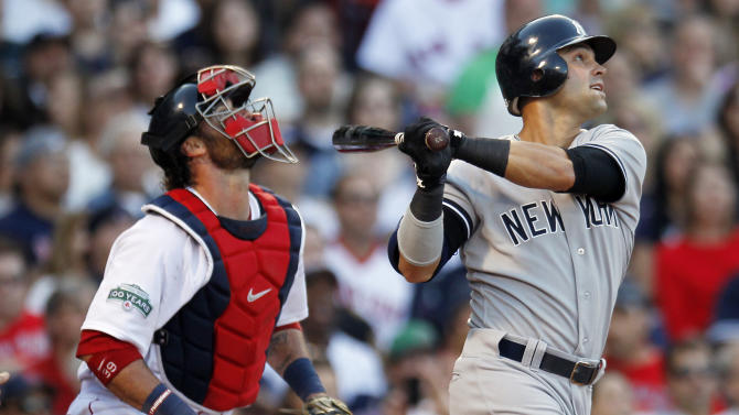 New York Yankees' Nick Swisher, right, watches his grand slam in front of Boston Red Sox's Jarrod Saltalamacchia in the seventh inning of a baseball game in Boston, Saturday, April 21, 2012. (AP Photo/Michael Dwyer)