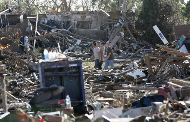 People walk through their tornado-ravaged neighbourhood in Moore