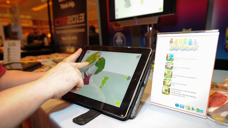 IMAGE DISTRIBUTED FOR DRIP DROPS - Journalists demoing the app seen at CES Showstoppers, on Tuesday, Jan. 8, 2013, in Las Vegas, Nevada, Drip Drops debuts Color the World app turning a tablet into a 3d digital coloring book for preschoolers. (Photo by Al Powers/Invision for Drip Drops/AP Images)
