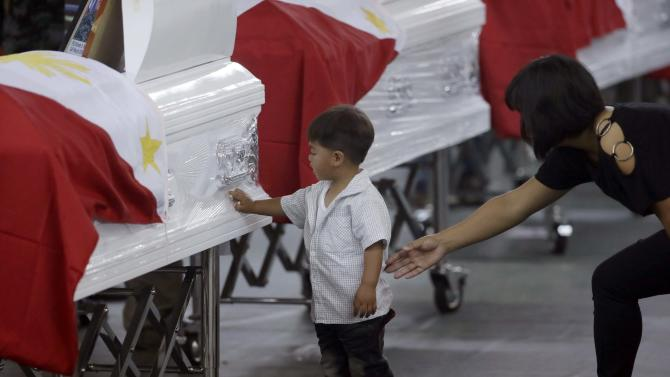 Christine Kiangan, widow of Noble Kiangan, one of the 44 members of the elite police commandos killed last Sunday during the Philippines' biggest single-day combat loss in recent years, reaches out to her son as he touches a commando's flag-draped coffin at Camp Bagong Diwa, Taguig city, south of Manila, Philippines, on Friday, Jan. 30, 2015.  On Friday, Philippine President Benigno Aquino III promised grieving relatives of the slain commandos that government forces will capture suspected bomb-maker Abdul Basit Usman. (AP Photo/Bullit Marquez)