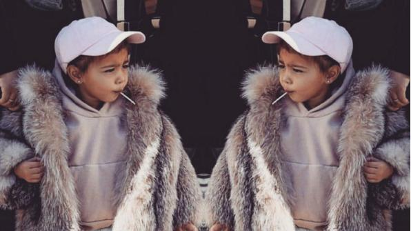 North West in a khaki sweatshirt, jeans and a fur coat.