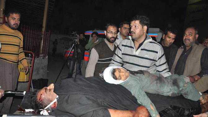 People look at dead bodies of a suicide attack victims, at a local hospital in Rawalpindi, Pakistan on Wednesday, Nov. 21, 2012. A suicide bomber had tried to enter a procession near a Shiite mosque, where the bomber detonated the explosives after being stopped by security forces killing or wounding scores of people, police officials said. (AP Photo/C.A. Hussain)