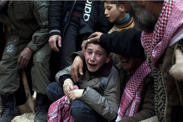 FILE - Ahmed, center, mourns his father Abdulaziz Abu Ahmed Khrer, who was killed by a Syrian Army sniper, during his funeral in Idlib, north Syria, Thursday, March 8, 2012. (AP Photo/Rodrigo Abd, Fil