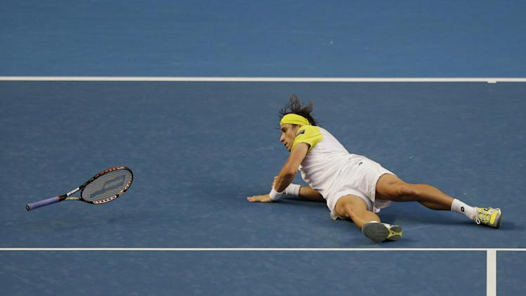 Spain's David Ferrer falls to the court during his first round match against Belgium's Oliver Rochus at the Australian Open tennis championship in Melbourne, Australia, Monday, Jan. 14, 2013. (AP Photo/Rob Griffith)