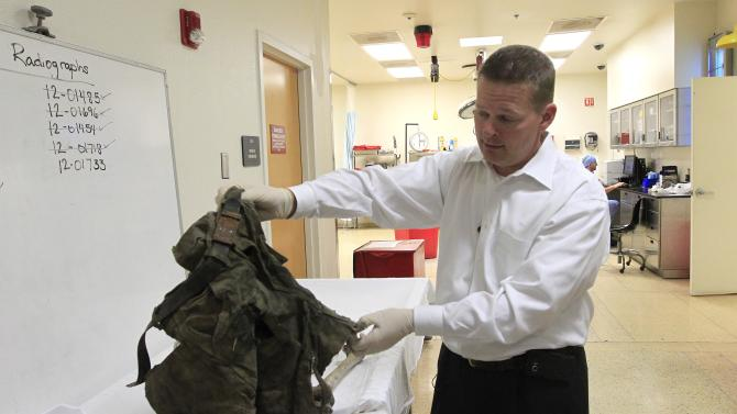 In this Aug. 10, 2012 photo, Dr. Gregory Hess, Chief Medical Examiner for Pima County, pulls out a pair of pants and a few bones from a small body bag, all that remains of an illegal immigrant found in the desert in Arizona at the Pima County morgue in Tucson, Ariz.  The death of migrants crossing the Southwest border has long been a tragic consequence of illegal immigration and, many say, the massive increase in U.S. border enforcement. For some, the tragedies are a powerful motivator in pushing Congress to act this year on a larger immigration reform package.  (AP Photo/Ross D. Franklin)