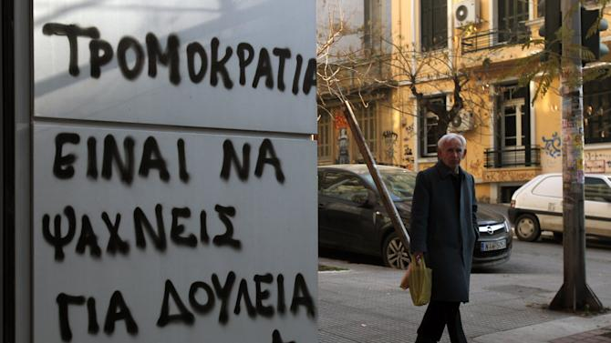 An elderly man passes graffiti that reads in Greek: ''Terrorism = Job Seeking'' in the northern Greek port city of Thessaloniki, Thursday, Jan. 10, 2013. Unemployment has reached new highs in Greece, with October 2012 figures showing the jobless rate at 26.8 percent, a major increase from the same month in 2011. (AP Photo/Nikolas Giakoumidis)