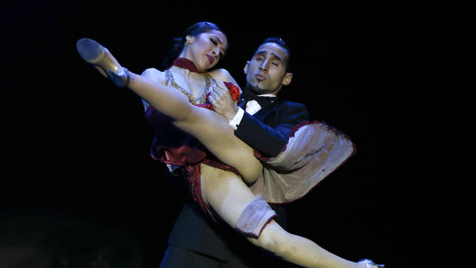Argentina's dancers Ariel Leguizamon and Yesica Esquivel, top, compete during the 2012 Tango Dance World Cup stage finals in Buenos Aires, Argentina, Tuesday, Aug. 28, 2012. Couples from around the world competed in the finals Argentina's annual tango competition, the highlight of a two-week festival which this year honored Astor Piazzolla, the legendary composer and bandoneonista who revived the genre and infuriated purists by blending tango with rock music in the 1970s. (AP Photo/Natacha Pisarenko)