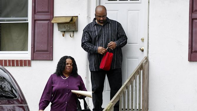 Anita Saunders, mother of two teenage brothers, Dante Robinson, 17, and Justin Robinson 15, who are charged in the murder of  Autumn Pasquale, 12, walks out of her home Thursday, October 24, 2012, in Clayton,. N.J., with her husband Richard Saunders.  According to Gloucester County prosecutor Sean Dalton, the boys' mother played a part in cracking the case involving Autumn Pasquale. She came forward with information about a posting on a son's Facebook account, leading police to the boys, Dalton said. (AP Photo/Mel Evans)