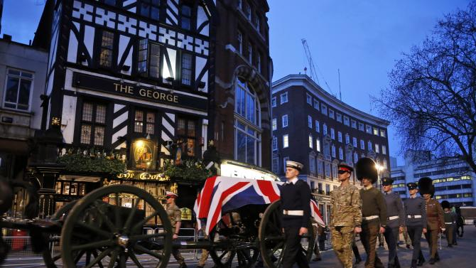 """British forces' officers escort a Union Jack-draped coffin on a gun carriage drawn by the King's Troop Royal Artillery during a rehearsal for the upcoming funeral of former British Prime Minister Margaret Thatcher in central London, early Monday, April 15, 2013. Thatcher, the combative """"Iron Lady"""" who infuriated European allies and transformed her country by a ruthless dedication to free markets in 11 bruising years as prime minister, died Monday, April 8, 2013. The funeral will take place Wednesday, April 17, 2013. (AP Photo/Lefteris Pitarakis)"""