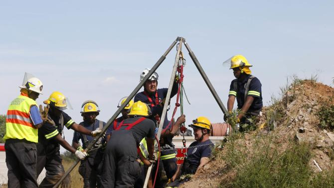 Rescue officials use hoists to remove debris as they work to rescue trapped suspected illegal miners from an abandoned gold shaft in Benoni