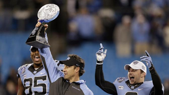 North Carolina head coach Larry Fedora, center, raises the trophy as he celebrates with Kareem Martin, left, and Ryan Switzer, right, after defeating Cincinnati in the Belk Bowl NCAA college football game in Charlotte, N.C., Saturday, Dec. 28, 2013. North Carolina won 39-17. (AP Photo/Chuck Burton)
