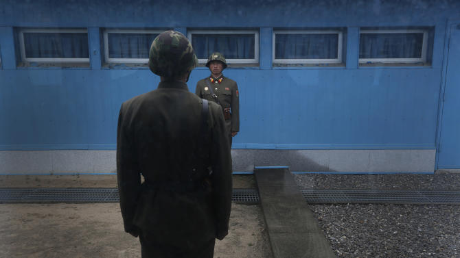 """North Korean soldiers stand guard on the demarcation line of the Demilitarized Zone that separates the two halves of the Korean peninsula at Panmunjom, North Korea Monday, April 23, 2012. North Korea promised Monday to reduce South Korea's conservative government """"to ashes"""" in less than four minutes, in an unusually specific escalation of recent threats aimed at its southern rival.   The statement by North Korea's military, carried by state media, comes amid rising tensions on the Korean peninsula. Both Koreas recently unveiled new missiles, and the North unsuccessfully launched a long-range rocket earlier this month. (AP Photo/Vincent Yu)"""