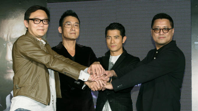 "In this photo taken on Monday, Nov. 12, 2012, Hong Kong director Sunny Luk,  left, actors Tony Leung Ka Fai, second from left, Aaron Kwok, center, and director Lok Man Leung pose for media during a promotional event for their new film ""Cold War"" in Taipei, Taiwan. (AP Photo/Chiang Ying-ying)"