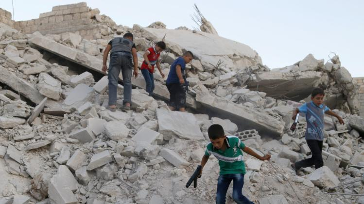 Boys hold toy guns as they play on the rubble of collapsed buildings during the Eid al-Fitr festival in Maarat Al-Nouman, south of Idlib
