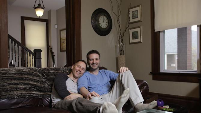 "In this Nov. 16, 2011 photo, Capt. Stephen Hill, left, and his partner, Joshua Snyder, pose for a photo in their home in Columbus, Ohio. Hill, the U.S. Army captain who was booed during a Republican presidential debate when he asked a question about ""don't ask, don't tell,"" just returned from a year-long deployment in Iraq, and says he wasn't trying to score political points, just peace of mind for himself and his husband of four-and-a-half months. (AP Photo/Jay LaPrete)"