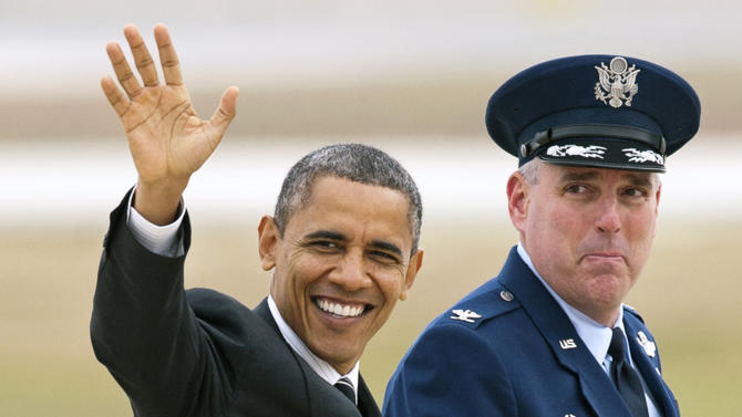 President Barack Obama, accompanied by Air Force Col. Michael A. Minihan, commander, 89th Airlift Wing, waves as he walks to Air Force One at Andrews Air Force Base, Md., Thursday, Nov. 15, 2012, en route to New York to visit areas devastated by Superstorm Sandy. (AP Photo/Cliff Owen)