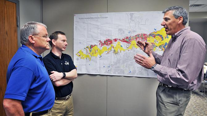 Wichita Falls, Texas Public Works Director Russell Schreiber, right, talks with Mayor Glenn Barham, left, and City Manager Darron Leiker, Monday, May 25, 2015, at the Emergency Operations Center about local flooding concerns and what is being done in affected areas of town. In the U.S., the weather system dumped record rainfall on parts of the Plains and Midwest, spawning tornadoes and causing major flooding that forced at least 2,000 Texans from their homes. (Torin Halsey/Times Record News via AP)