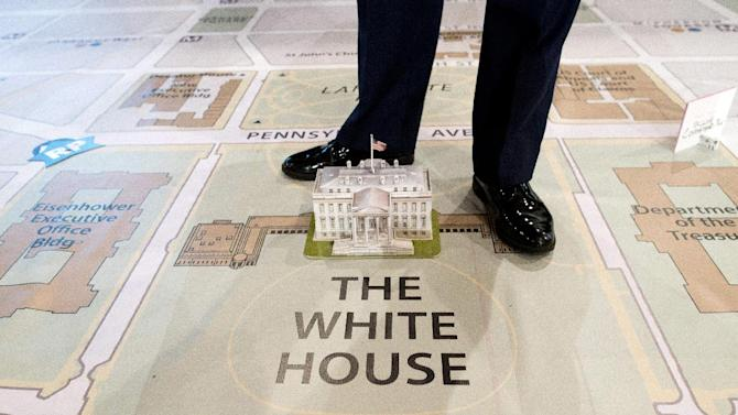 A member of Joint Task Force-National Capital Region stands over a model of the White House on a giant map during a media tour highlighting inaugural preparations being made by military and civilian planners, Wednesday, Dec. 12, 2012, at the DC Armory in Washington.  (AP Photo/ Evan Vucci)