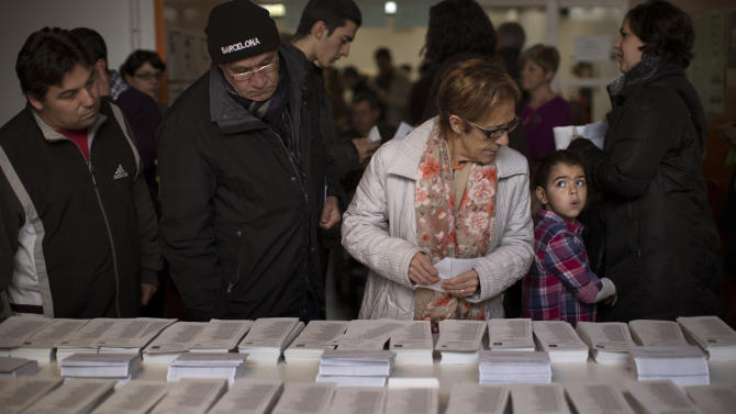 Voters choice their ballot papers to cast their votes in a polling station in Barcelona, Spain, on Sunday, Nov. 25, 2012. Voters in Catalonia begin casting their ballots in regional elections that could determine the future shape of Spain. If voters give the regional government strong support, its leader pledged to hold a referendum asking Catalans if they'd prefer to split from Spain and go it alone in the 27-member EU. (AP Photo/Emilio Morenatti)