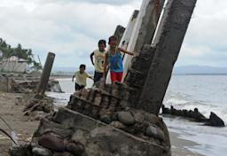 Boys walk among the ruins of a building destroyed …