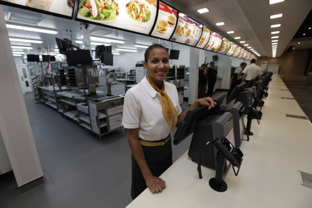 Rachel Lucian, assistant manager of the newly constructed McDonald&#39;s restaurant at the Olympic Park in east London, poses for the photographers, Monday, June 25, 2012. The restaurant is designed to be reusable and recyclable after the London 2012 Olympic and Paralympic Games. (AP Photo/Lefteris Pitarakis)