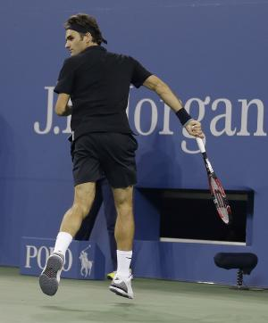 Roger Federer, of Switzerland, looks back after hitting a shot between his legs against Marinko Matosevic, of Australia, during the first round of the U.S. Open tennis tournament Tuesday, Aug. 26, 2014, in New York. (AP Photo/Darron Cummings)
