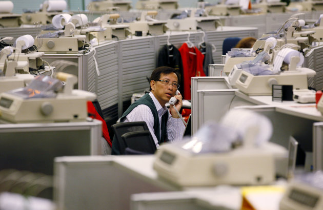 A floor trader talks on the phone at the Hong Kong Stock Exchange Tuesday, April 24, 2012. Unsettling news about Europe's debt crisis and disappointing U.S. corporate earnings weighed on Asian stock markets Tuesday. Hong Kong's Hang Seng lost 0.2 percent at 20,591 after a higher opening. (AP Photo/Kin Cheung)