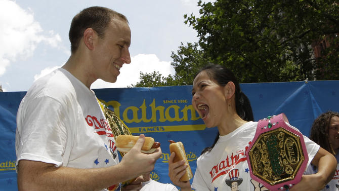 """Women's hot-dog eating record-holder, Sonya """"The Black Widow"""" Thomas, right, challenges five-time hot-dog eating world champion Joey Chestnut, left, during a weigh-in for contestants in the annual Coney Island Fourth of July international hot-dog eating contest, Tuesday, July 3, 2012, at City Hall Park in New York.  The event will take place midday Wednesday, July 4, at Coney Island, Brooklyn.  Chestnut will try to break his own world record of downing 68 hot dogs and buns in 10 minutes.  Thomas, who weighs 100 pounds, will headline the women's competition, facing 14 female eaters from the U.S. and Canada. (AP Photo/Kathy Willens)"""