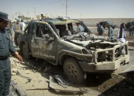An Afghan police officer, left, looks at a police vehicle damaged in a suicide attack in Lashkar Gah, Helmand province, Afghanistan, Tuesday, Sept. 27, 2011. A suicide bomber rammed a car packed with explosives into a police truck outside a bakery in southern Afghanistan on Tuesday, killing a number of civilians, officials said. (AP Photo/Abdul Khaleq)