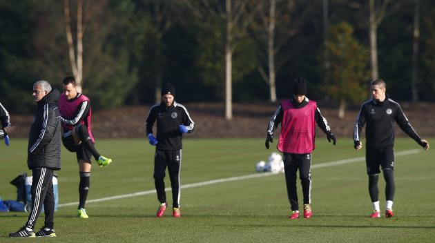 Chelsea's manager Jose Mourinho talks to a member of his staff as players warm up behind him during a training session at the team training facility in Stoke D'Abernon to the south of London