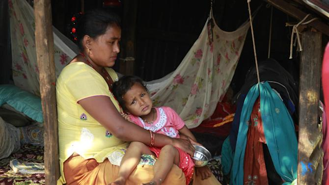 In this photo taken on Saturday, May 2, 2015, Namaya Shretha, 25, sits in a makeshift shelter with her daughter in the destroyed village of Pokharidanda, near the epicenter of the April 25 massive earthquake, in the Gorkha District of Nepal. People in villages reachable by road in Nepal's quake-wracked central Gorkha District are fending for themselves, with the government so short on relief they've been forced to focus only on far-flung reaches of the remote Himalayas. (AP Photo/Wally Santana)