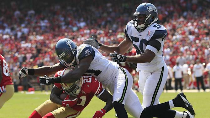 San Francisco 49ers running back Frank Gore (21) is tackled by Seattle Seahawks defensive back Kam Chancellor (31) as linebacker K.J. Wright (50) closes in the second quarter of an NFL football game in San Francisco, Sunday, Sept. 11, 2011. (AP Photo/Marcio Jose Sanchez)