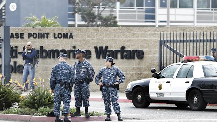 Military police stand guard outside Naval Base Point Loma in San Diego as San Diego police officers and federal agents search for former Los Angeles officer Christopher Dorner who police believe is responsible for three murders Thursday Feb. 7, 2013.  (AP Photo/Lenny  Ignelzi)